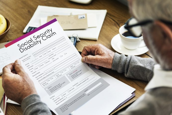 elderly man with glasses holding a social security disability claim form