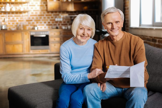 couple sitting on a couch and holding paperwork
