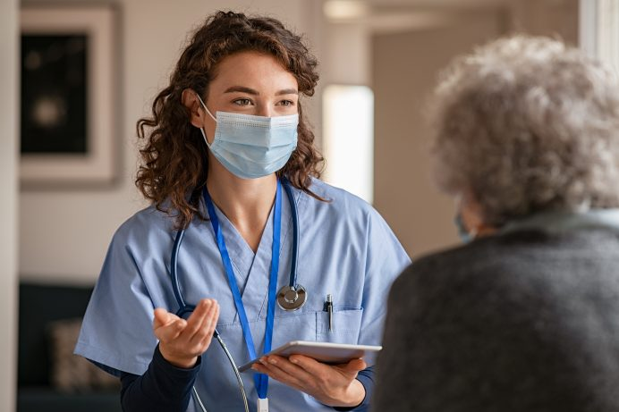 nurse wearing a mask speaking to a patient