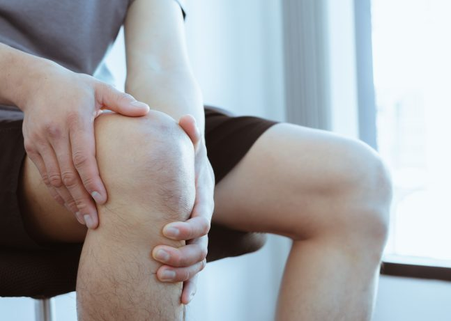 man suffering from knee pain due to overexertion