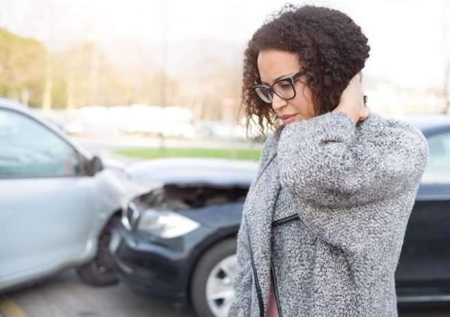 african american woman getting neck pain because of getting in a car accident