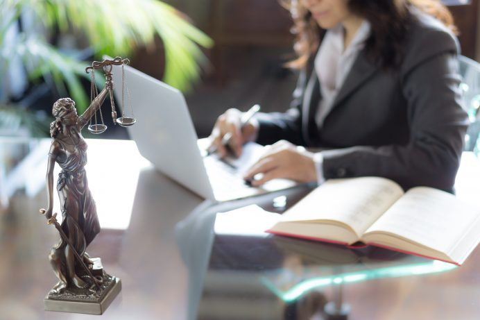 a laywer's desk with statue of justice with scales and a lawyer looking doing work on a laptop