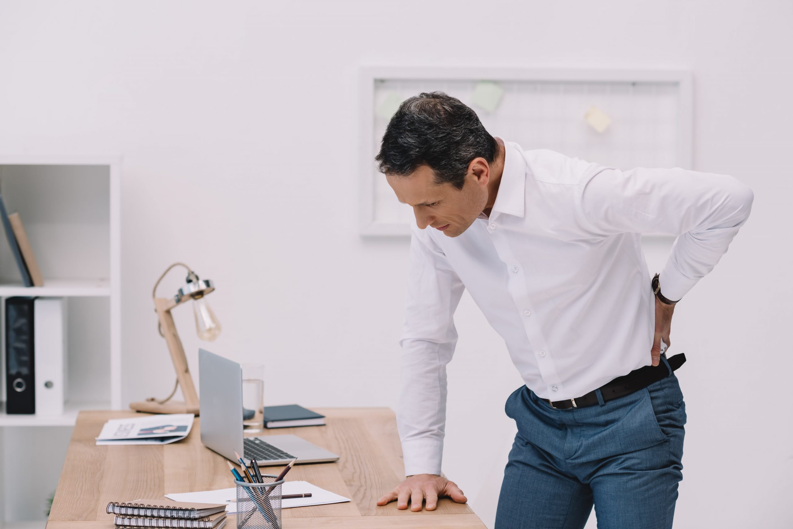 mature businessman at his work desk with lower back pain