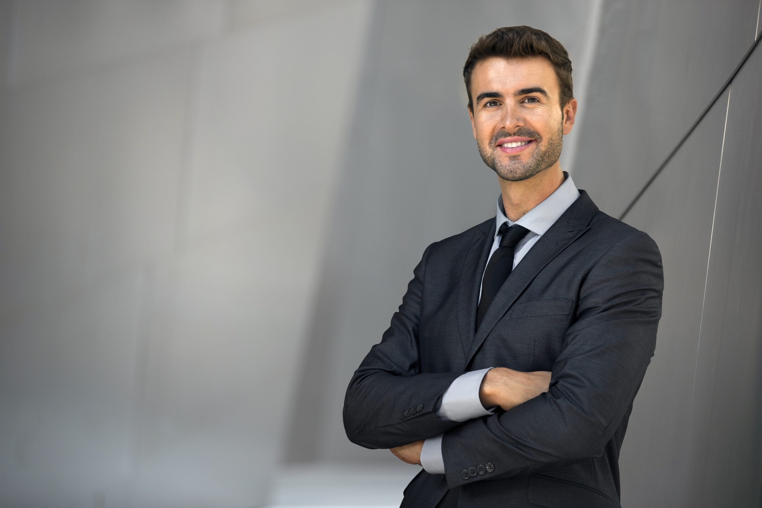 male attorney standing outside and posing for a photo with arms crossed