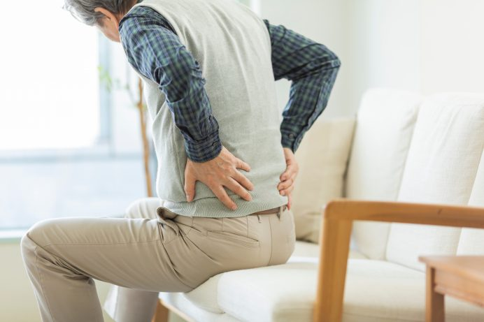 senior man wearing a vest and khaki pants sitting on a white couch with back pain