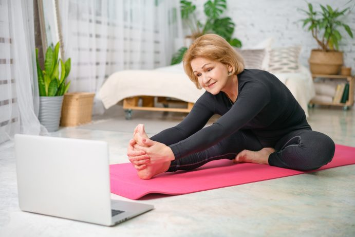 middle aged woman wearing black doing yoga at home during work break