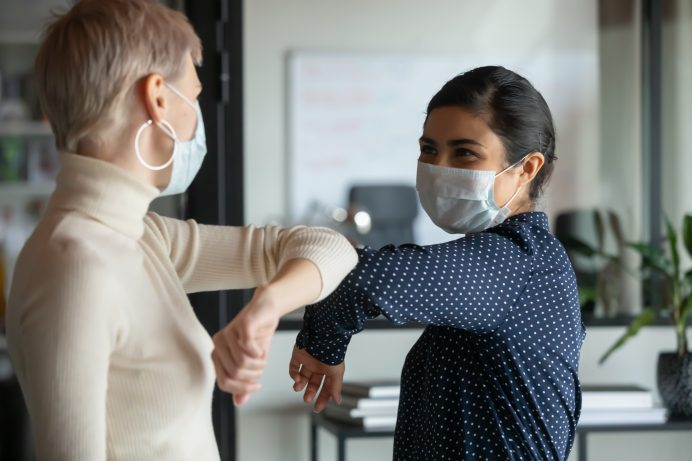 mexican american employee bumping elbows with a caucasian female coworker at office wearing masks
